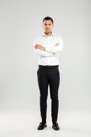 Full lenght image of serious young man dressed in white shirt isolated over grey wall background. Looking at camera with arms crossed.