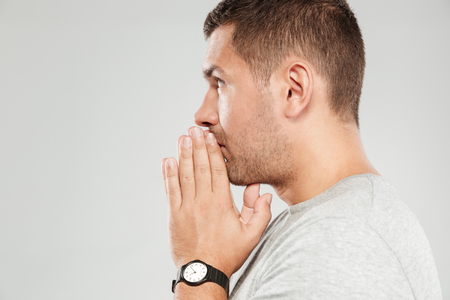 Image of young concentrated man dressed in grey t-shirt isolated over grey wall. Looking aside and prays. Stok Fotoğraf