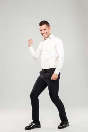 Cheerful young man dressed in white shirt isolated over grey wall background. Looking camera make winner gesture.