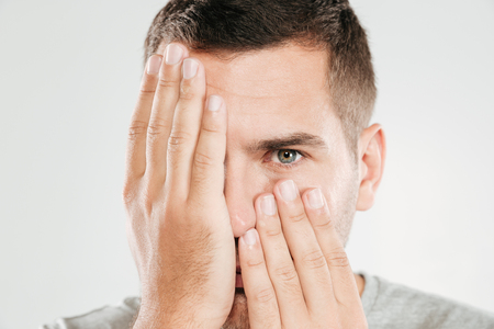 Image of young man dressed in grey t-shirt isolated over grey wall covering face with hands. Looking camera. Stok Fotoğraf