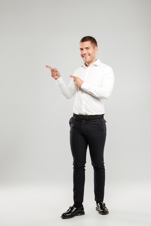 Full-lenght photo of cheerful young man dressed in white shirt isolated over grey wall background pointing to copyspace. Looking camera.