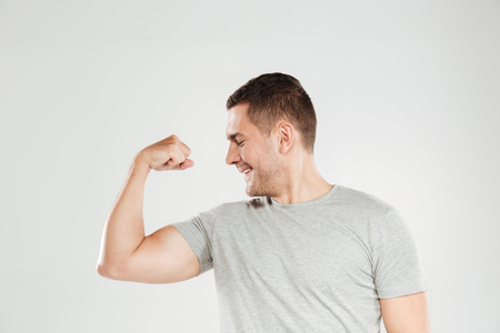 Image of young emotional man dressed in grey t-shirt isolated over grey wall background showing biceps. Looking aside. Stok Fotoğraf