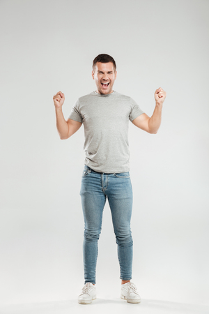 Image of excited young man dressed in grey t-shirt isolated over grey wall background make winner gesture. Looking at camera.