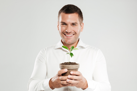 Photo of young smiling man dressed in white shirt isolated over grey wall background. Looking camera while holding plant.