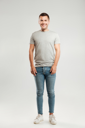 Full lenght picture of happy young man dressed in grey t-shirt isolated over grey wall background. Looking at camera.