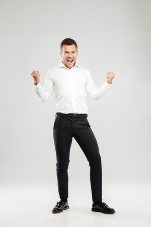 Image of screaming emotional young man dressed in white shirt isolated over grey wall background. Looking camera make winner gesture.