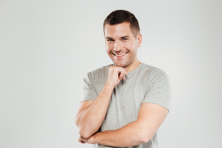 Happy young man dressed in grey t-shirt isolated over grey wall background. Looking at camera. Stock Photo