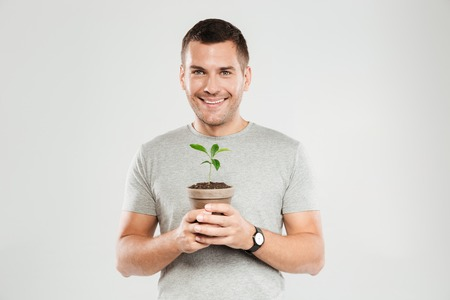 Photo of young smiling man dressed in grey t-shirt isolated over grey wall background. Looking camera while holding plant.