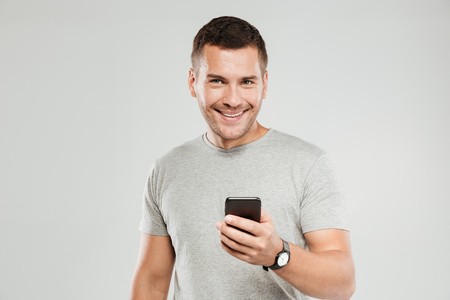 Image of young happy man dressed in grey t-shirt isolated over grey wall background. Looking camera while using mobile phone chatting.