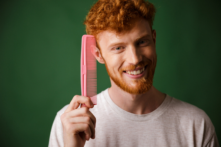 Smiling young readhead beardy man showing pink comb, over green background
