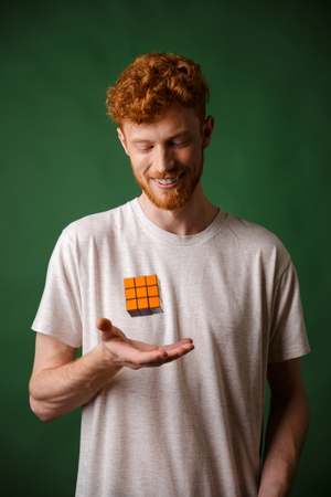 Shot of young smiling readhead bearded man, holding Rubiks Cube, over green background Stok Fotoğraf