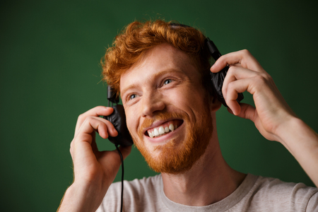 Young curly readhead bearded man is enjoying listening to music, over green background
