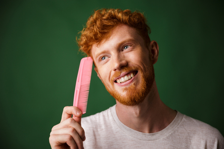Close-up portrait of smiling young readhead beardy man with pink comb, over green background Banco de Imagens
