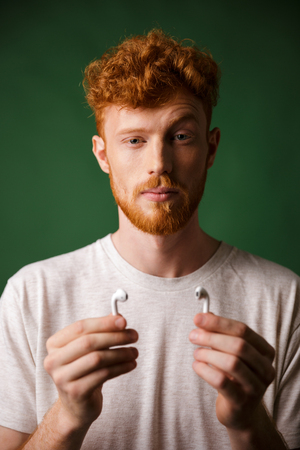 Close-up portrait of curly redhead man with raised eyebrow, showing his airpods, over green background