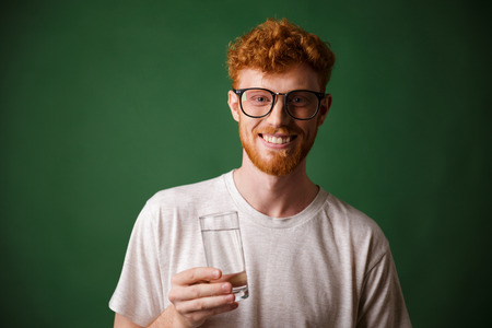 Cheerfull readhead bearded man in glasses, holding glass of water, over green background