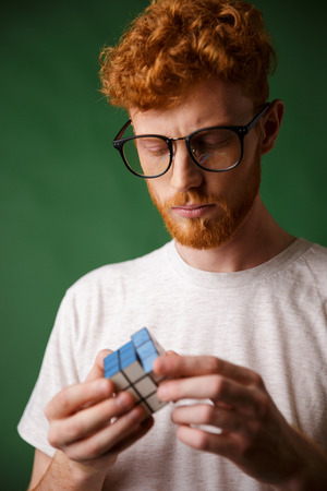 Close-up photo of concentrated readhead guy in glasses, playing with rubics cube, over green background Stock Photo