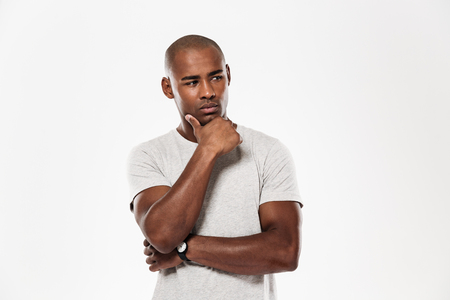 Image of serious young african man standing isolated over white background. Looking aside.