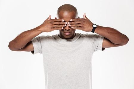 손으로 얼굴을 다루는 흰색 배경 위에 절연 서 젊은 아프리카 남자의 이미지.