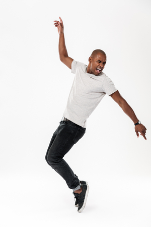 Photo of emotional young african man dancing isolated over white background. Looking aside.