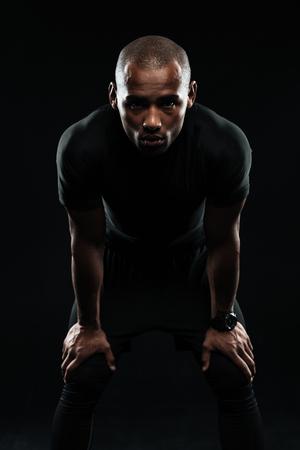 Sérieux, afro-américain, sport, debout, mains, genoux, regarder appareil-photo