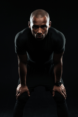 Serious afro american sports man standing with his hands on knees, looking at camera isolated on a black background Stock Photo