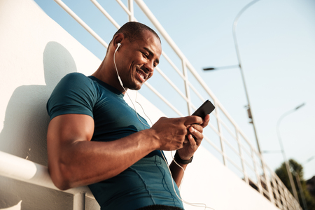 Portrait of a smiling afro american sportsman listening to music with earphones while using mobile phone and leaning on a wall outdoors Stok Fotoğraf