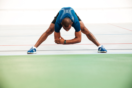 Full length portrait of a young sportsman doing stretching exercises on a track field outdoors