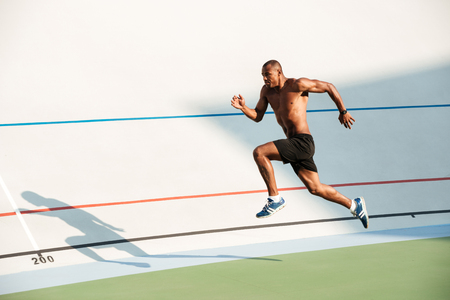 Full length portrait of a athletic half naked sportsman jumping on a track field outdoors Stock Photo