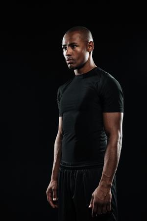 Jonge afro Amerikaanse sport man, wegkijken, geïsoleerd op zwarte achtergrond Stockfoto