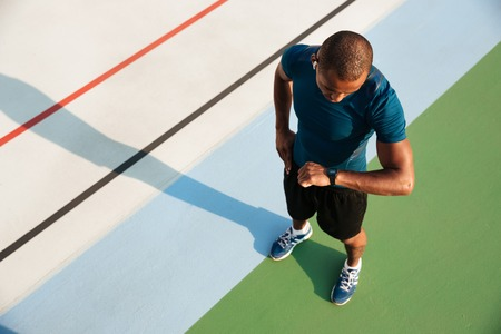 Top view of a young african sportsman looking at his wrist watch while standing on a track field