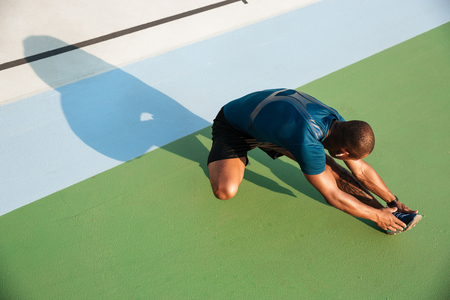 Top view portrait of a young african sportsman doing stretching exercises on a track field outdoors