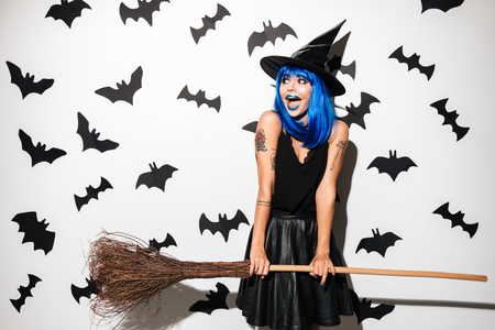 Photo of emotional screaming young woman in witch halloween costume on party over white background with broom.