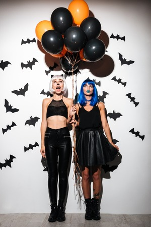Image of two emotional young women in halloween costumes on party over white background with balloons. Looking aside. Stock Photo