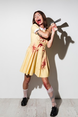 hemorragias: Full image image of happy screaming zombie woman in dress attacking with an axe and closed eyes over white background Foto de archivo