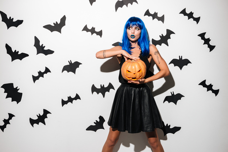 Photo of emotional amazing young woman in witch halloween costume on party over white background with pumpkin. Looking aside.
