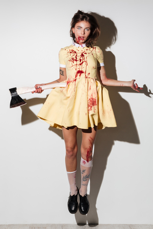Full length image of young frightening zombie woman in dress like flying with an axe in hand and looking at the camera over white background