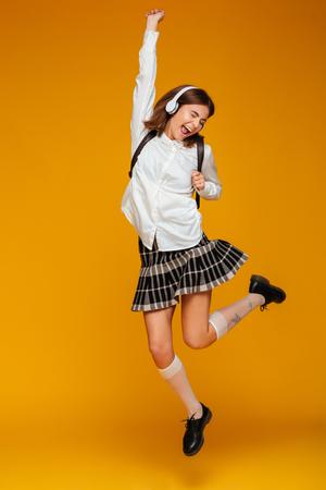 オレンジ色の背景に分離されたヘッドフォンの音楽を聴きながらジャンプで制服を着た幸せな 10 代女子高生の完全な長さの肖像画