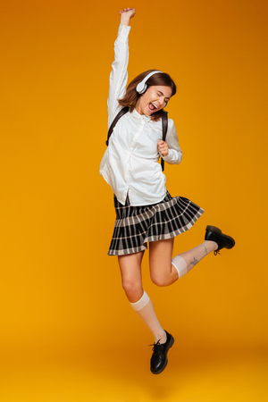 Full length portrait of a happy teenage schoolgirl in uniform with headphones jumping while listening to music isolated over orange background