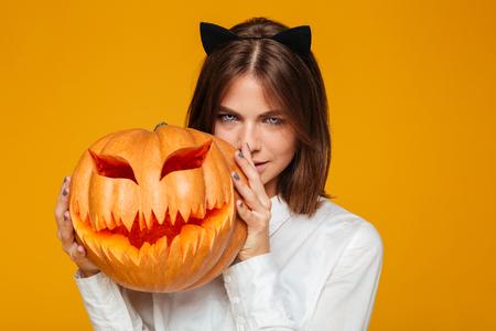 심각한 젊은 여자의 이미지 미친 고양이 호박와 노란색 배경 위에 할로윈 의상을 입고.
