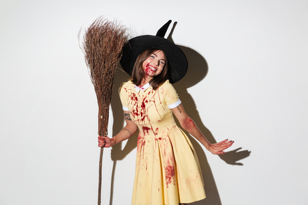 Smiling woman in halloween costume like witch holding broom and looking at the camera over white background Stock Photo