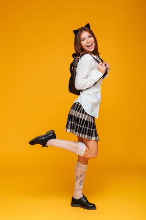 Full length portrait of a teenage schoolgirl in uniform with backpack standing and looking at camera isolated over orange background