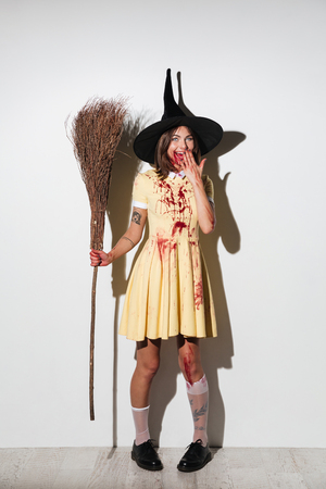 Full length image of happy woman in halloween costume holding broom and covering her mouth over white background Stock Photo