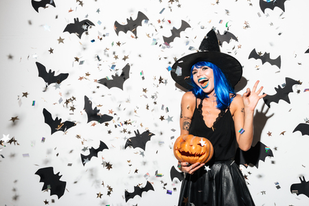 Picture of emotional young woman in halloween costume on party over white background with pumpkin. Looking camera showing ok gesture. 스톡 콘텐츠