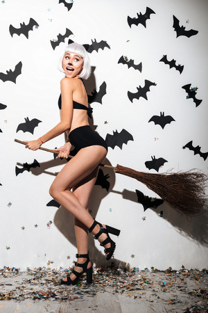 Picture of attractive young woman in halloween costume cat on party over white background with broom. Looking aside.