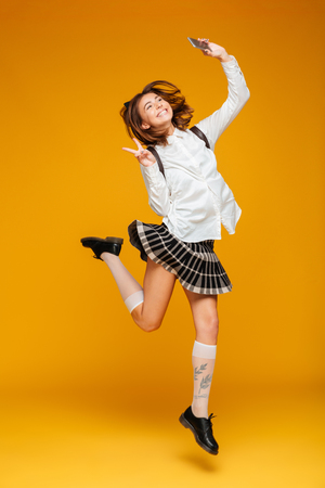 Full length portrait of an excited teenage schoolgirl in uniform with backpack taking a selfie while jumping and showing peace gesture isolated over orange background