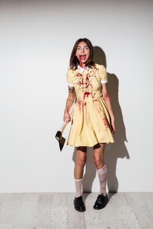 斧を押し、白い背景の上のカメラを見て怒って幸せゾンビ女の全身画像をドレスします。