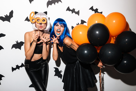 Image of two emotional young women in halloween costumes on party over white background with balloons. Looking camera. Stock Photo