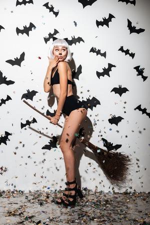 Beeld van aantrekkelijke jonge vrouw in Halloween-kostuumkat op partij over witte achtergrond met bezem. Opzij kijken.