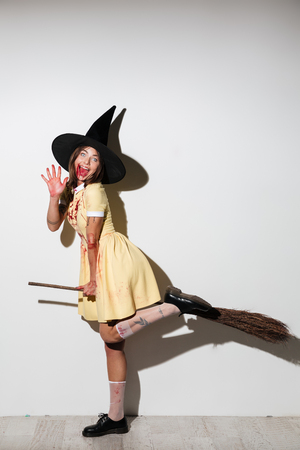 Full length image of happy woman in halloween costume with open mouth flying on broom like witch and looking at the camera over white background Stock Photo