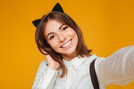 Close up portrait of a smiling teenage schoolgirl in uniform with backpack taking a selfie while standing and posing isolated over orange background